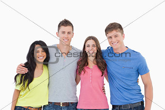 Four friends smiling and embracing each other as they look into