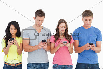 Four people standing beside each other and texting on their phon