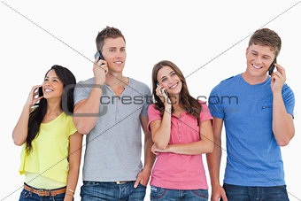Four people all on their phones as they stand beside each other