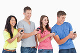 Four laughing friends sending texts on their phones