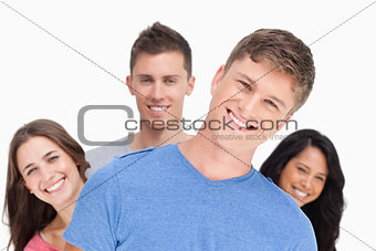 A man smiling with his head tilted and his friends behind him