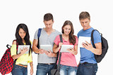 Students with backpacks looking at their tablets