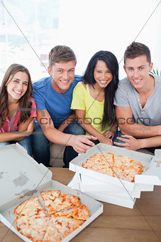 Friends sitting on a couch about to eat pizza