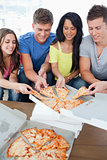 A group grabbing themselves a slice of the pizza