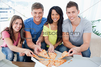 A group of friends taking a slice of pizza each as they look at