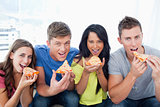 People about to eat pizza as they look at the camera