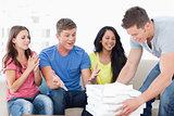 Friends celebrating as one guy brings pizza to them