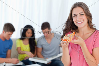 A smiling girl with a slice of pizza in front of her friends