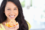 A smiling woman holding a slice of pizza as she looks at the cam