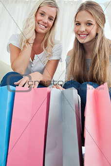 Close of bags with girls above them smiling