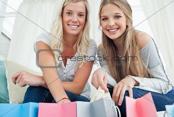 Girls smiling as they look at the camera with bags