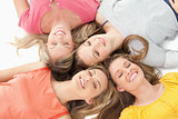 Four girls with their eyes closed and smiling while on the groun