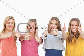 Four smiling girls giving the thumbs up