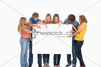 A group holding a blank sheet and pointing to it