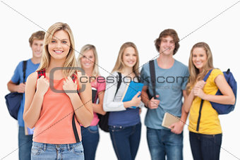 A smiling girl stands in front of her college friends