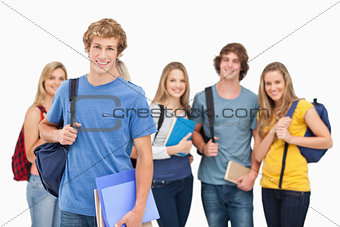 A group of smiling college students look into the camera as one