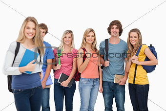 A girl standing in front of her college friends as they all smil