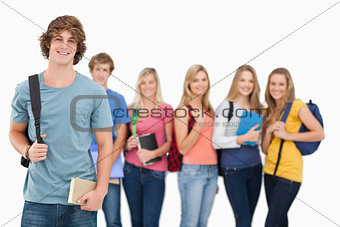 A man standing in front of his friends as he smiles