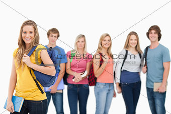 A woman standing in front of his friends as she smiles