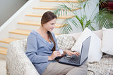 Women sitting on a sofa while using a laptop