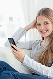 A smiling girl holds a phone in her hand as she looks at the cam