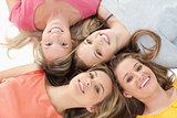 Four girls smiling as they lie on the floor together