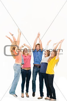 Group of friends cheering as they jump in the air and look at on