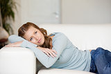 Woman lying on a sofa while crossing her arms