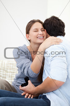 Couple embracing eachother while holding a jewel case