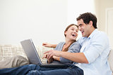 Couple laughing while typing on a computer