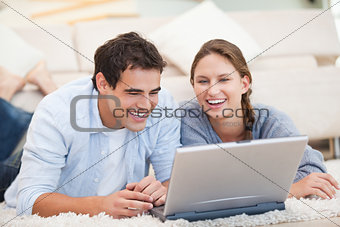 Young Couple lying while using a computer