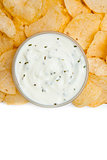 Close up of a bowl of white dip with herbs surrounded by nachos