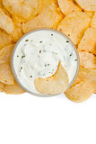 Close up of a bowl of dip with herbs and a nacho dipped in it