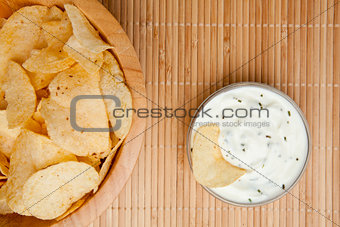 A bowl of chips and a bowl of dip side by side
