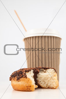 An half eaten doughnut and a cup of coffee placed together