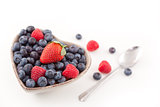 Berries in  a heart shaped bowl with spoon