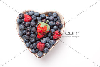 Different berries in  a heart shaped bowl
