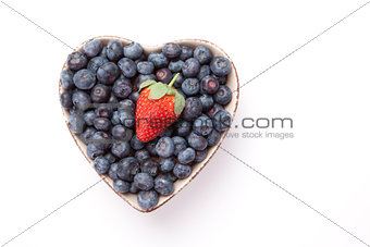 Blueberries and one Strawberry  in  a heart shaped bowl