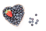 One strawberry and bluberries in  a heart shaped bowl
