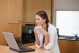 Woman holding a cup while looking at a computer