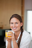 Woman drinking orange juice while smiling