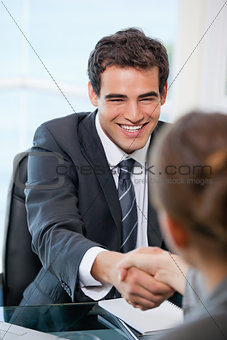 Businessman shaking hands with a client while smiling