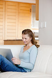 Woman sitting on a sofa while looking at laptop