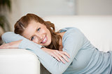 Smiling Woman crossing her arms while lying on a sofa 