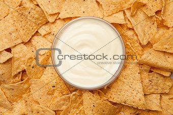 Bowl of dip placed among nachos