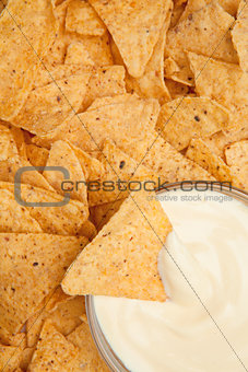 Bowl of dip surrounded by nachos