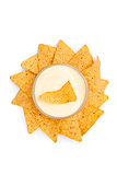 Bowl of white dip surrounded by nachos