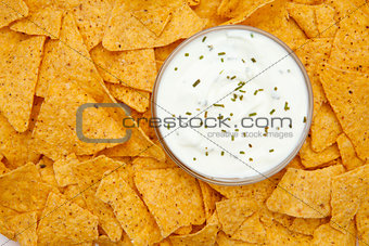 Bowl of dip with herbs surrounded by nachos
