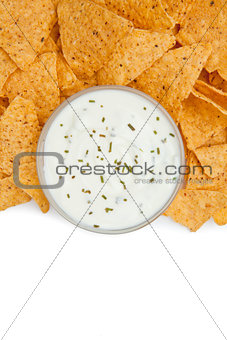 Close up of a bowl of dip with herbs surrounded by nachos