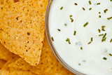 Close up of a bowl of white dip  beside nachos